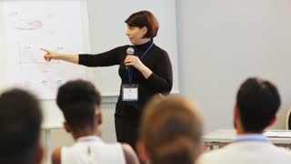 business, education and strategy concept - businesswoman with microphone and charts on whiteboard talking to group of people at conference presentation