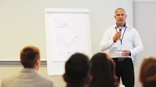 business, education and strategy concept - smiling businessman with microphone and charts on whiteboard talking to group of people at conference presentation