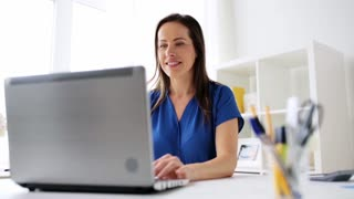 business, freelance, people and technology concept - happy smiling woman with laptop computer having video conference at home or office