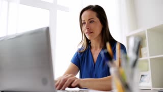 business, freelance, people and technology concept - tired woman with laptop computer working at home or office