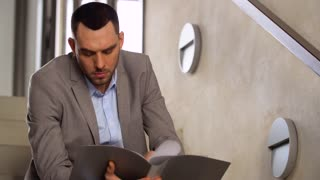 business, people and corporate concept - businessman with folder sitting on stairs