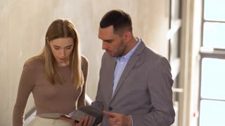 business, people and corporate concept - businesswoman and businessman discussing documents in folder at office