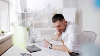 business, people, paperwork and technology concept - businessman with smart watch and papers calling on smartphone at office