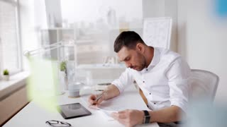 business, people, paperwork and technology concept - businessman with tablet pc computer and papers working at office