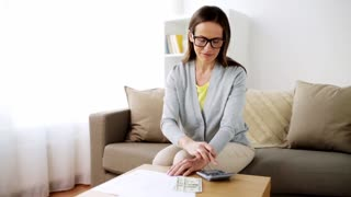 business, savings, finances and people concept - woman with money, papers and calculator at home