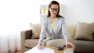 business, savings, finances, income and people concept - woman with papers and calculator counting money at home