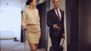 business trip and people concept - man and woman with travel bags walking along hotel corridor