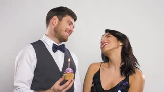 celebration and holidays concept - happy couple with birthday cupcake