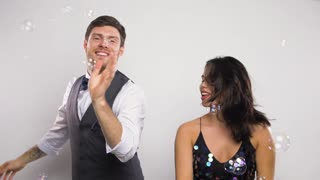 celebration, fun and holidays concept - happy couple dancing in soap bubbles at party