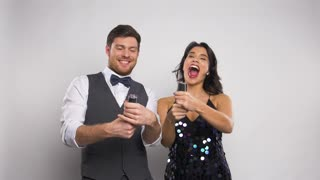 celebration, fun and holidays concept - happy couple popping party poppers