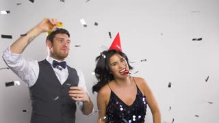 celebration, fun and holidays concept - happy couple with party blowers and caps