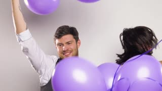 celebration, fun and holidays concept - happy couple with purple balloons dancing at birthday party