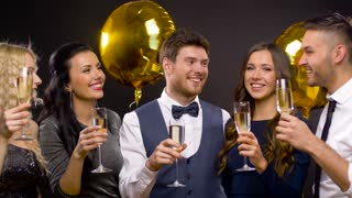 celebration, luxury and holidays concept - happy friends with golden balloons and champagne glasses at party over black background