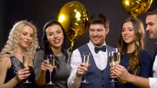 celebration, luxury and holidays concept - happy friends with golden balloons clinking champagne glasses at party over black background