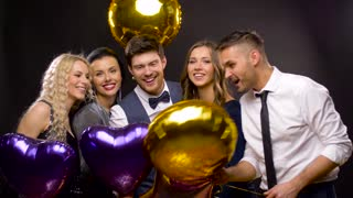 celebration, party and holidays concept - happy friends golden and violet balloons over black background