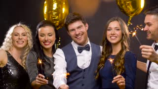 celebration, people and holidays concept - happy friends at christmas or new year party with sparklers and golden balloons over black background