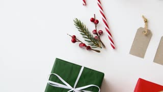 christmas and holidays concept - wrapped gift boxes, name tags and decorations on white background