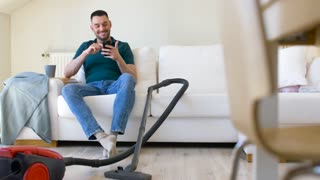 cleaning, household and technology concept - happy man with smartphone and vacuum cleaner at home