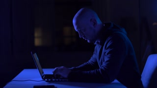 cybercrime, hacking and technology crime - male hacker in dark room writing code or using computer for cyber attack
