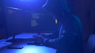 cybercrime, hacking and technology crime - male hacker in dark room writing code or using computer virus program for cyber attack