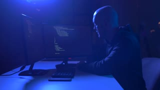 cybercrime, hacking and technology crime - male hackers in dark room with code on computer screen using virus program for cyber attack