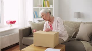 delivery, mail, shipping and people concept - senior woman opening parcel box at home