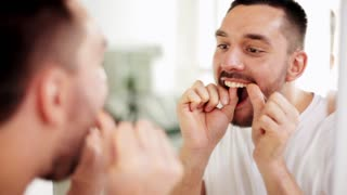 dental hygiene, people and beauty concept - man with floss cleaning teeth and looking to mirror at home bathroom