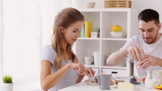 eating and people concept - happy couple having breakfast at home