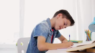 education, childhood and people concept - happy boy with book writing to notebook at home