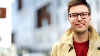 emotion, expression, vision and people concept - close up happy smiling man in eyeglasses outdoors
