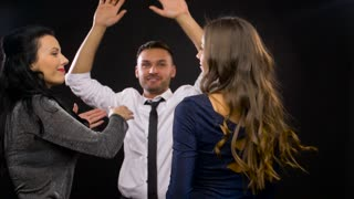 entertainment, night life and people concept - happy friends dancing at party or disco over black background