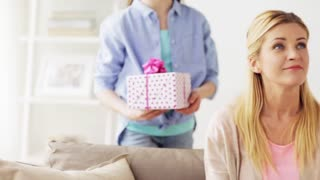 family and holidays concept - happy girl giving present to mother at home