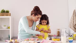 family, cooking and people concept - mother and little daughter making and decorating cupcakes with sprinkles at home kitchen