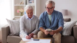 family, savings, old age and people concept - smiling senior couple with money, bills and calculator at home