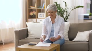 finances, savings, annuity insurance and people concept - senior woman with calculator and bills counting dollar money at home