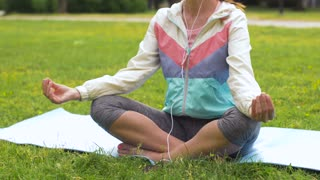 fitness, sport and healthy lifestyle concept - woman with smartphone and earphones meditating on yoga mat at park