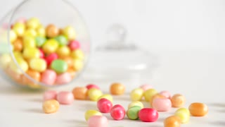 food, confectionery and sweets eating concept - close up of scattered candy drops and jar on table