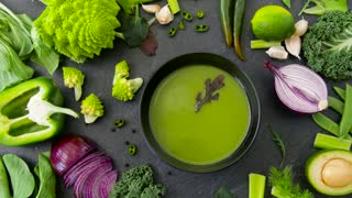 food, culinary and healthy eating concept - close up of vegetable green cream soup in bowl with arugula and spoon on kitchen table