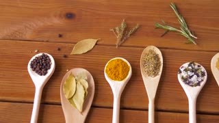 food, culinary and unhealthy eating concept - spoons with different spices on wooden table