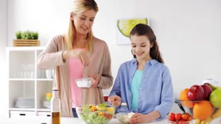 food, healthy eating, family and people concept - happy mother and daughter cooking and seasoning vegetable salad for dinner at home kitchen
