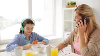 food, healthy eating, family and people concept - happy mother and daughter with smartphones and headphones having breakfast at home kitchen