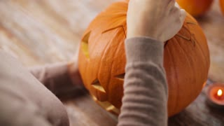 halloween, decoration and holidays concept - close up of woman putting burning candle into carved pumpkin or jack-o-lantern at home