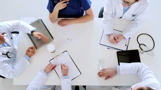 healthcare and medicine concept - group of doctors with cardiogram on clipboard at hospital