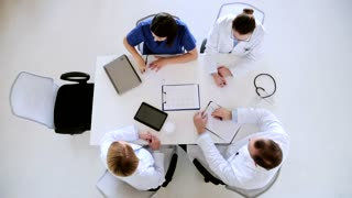 healthcare and medicine concept - group of doctors with clipboards and tablet pc computer discussing medical report at hospital