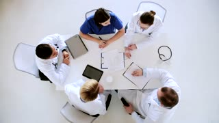 healthcare and medicine concept - group of doctors with medical report and cardiogram on clipboard at hospital