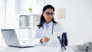healthcare, technology people and medicine concept - female doctor in white coat with laptop computer and papers at hospital
