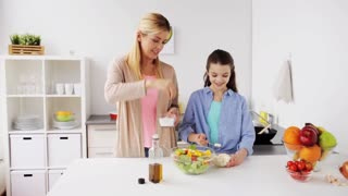 healthy eating and family concept - happy mother and daughter cooking and seasoning vegetable salad for dinner at home kitchen
