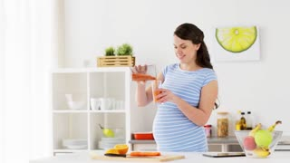 healthy eating, cooking, pregnancy and people concept - pregnant woman pouring fruit smoothie to glass and drinking at home kitchen