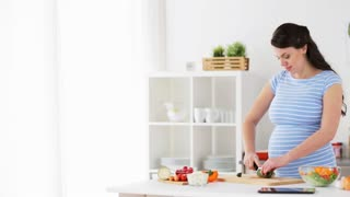 healthy eating, pregnancy, food and people concept - pregnant woman cooking vegetable salad and chopping cucumber at home kitchen