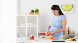 healthy eating, pregnancy, food and people concept - pregnant woman cooking vegetable salad and chopping pepper at home kitchen